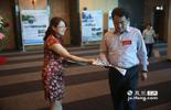 图为在会场外香港商报江西记者站的负责人郭美勤,把大会特刊内容派发给会场上的嘉宾。