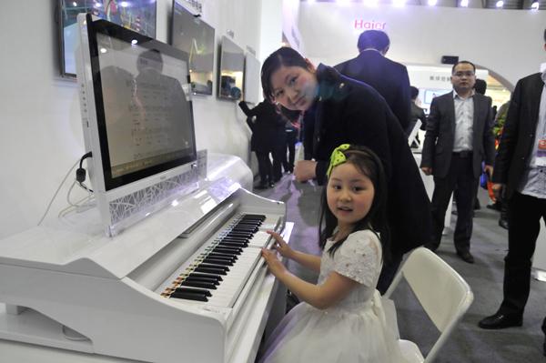 在家博会现场,小朋友在体验海尔智能钢琴一体机