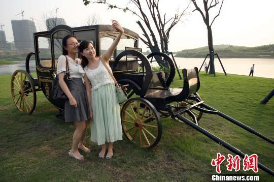 两名参加活动的女孩与英国传统的马车合影。郭晋嘉 陈超 摄
